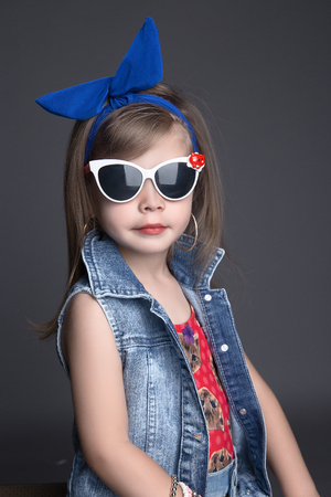 funny child girl in big blue bow and sunglasses. children shopping. fashionable little girl