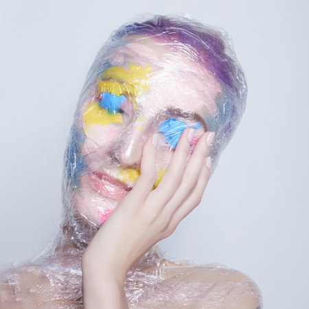 young woman with paint on her face in plastic. color painted girl in packing polyethylene.halloween body art