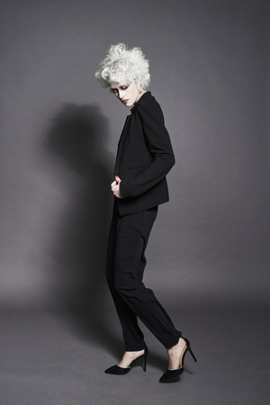 stylish girl in suit and heels shoes.fashion young woman with white skin and hair with clown make-up.halloween make-up