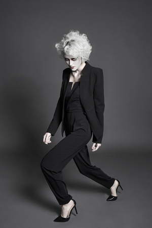 fashion young woman with white skin and hair with clown make-up.halloween make-up style girl in suit and heels shoes