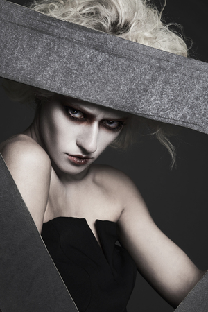 halloween style girl with white skin and hair with clown make-up posing in the studio.psycho woman image Stock Photo