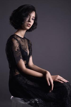 beautiful young woman in evening black dress sitting on stool.sexy beauty brunette girl Reklamní fotografie - 93939195