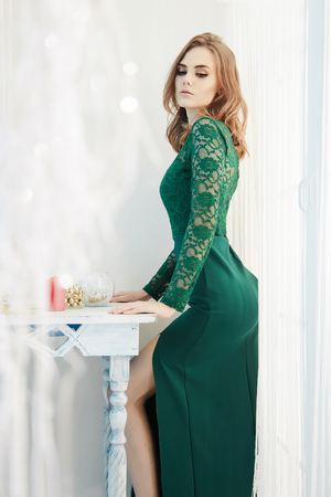 beautiful young woman at home. girl in green sexy dress stay near the window at festive home.beauty Elegant fashion glamour lifestyle photo in interior