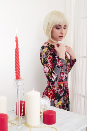 beautiful young woman in festive interior. elegant blond lady with bob hair, at home. New Year celebration
