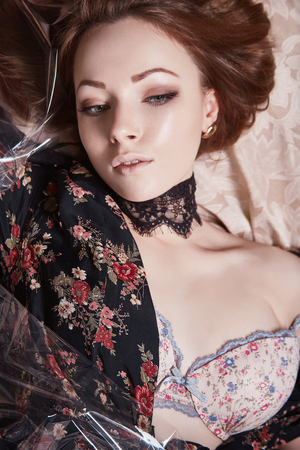 beautiful girl in black dress with flowers under polyethylene. sensual young woman lying in flower fabrics