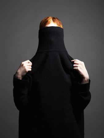 woman in black turtleneck. red hair girl posing in studio Stock fotó