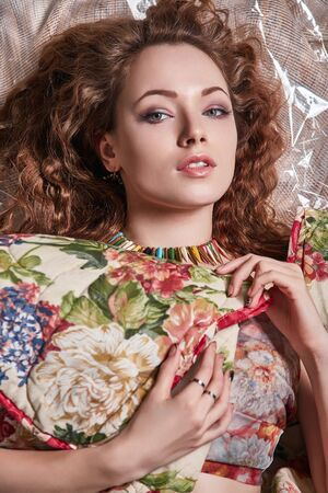 Happy young Woman with Make-up and Curly Hair style. sensual Beautiful Girl in Flower cloth Stock Photo