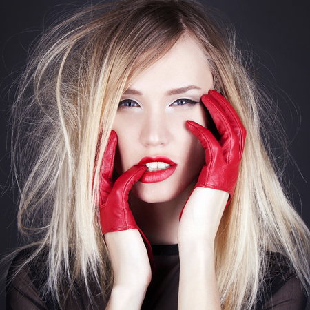 Fashion studio photo of beautiful girl with red gloves and red lips. Blond Young Woman Stock Photo