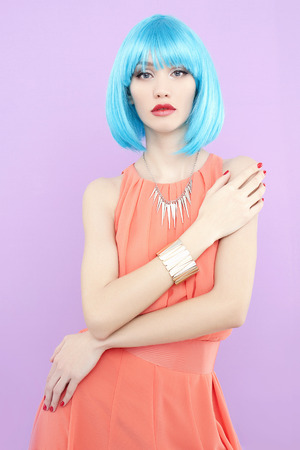 young woman with blue hair. Beautiful girl over pink background