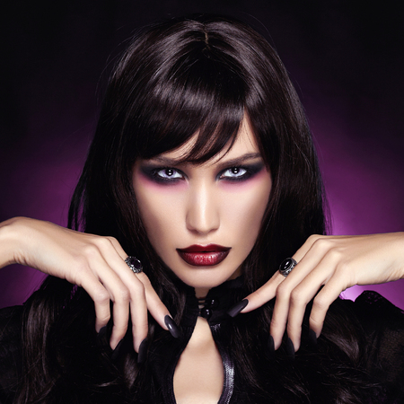 beautiful young vampire woman. black haired sexy Halloween Girl over dark purple background Stock Photo