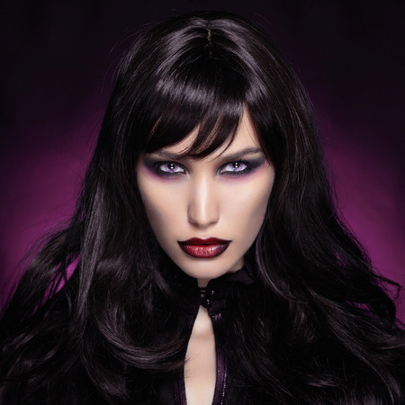 beautiful young vampire woman. black haired Halloween Girl over dark purple background