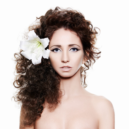 pure make-up, young woman with orchid flower.Curly Hairstyle Girl