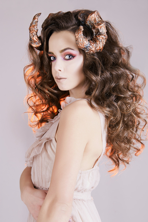 beautiful young woman with Horns. Curly Hairstyle Girl, make-up Stock Photo