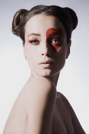 Beautiful woman with heart make-up. Beauty girl, painted heart on the face