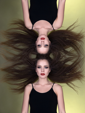 beautiful girl and her reflection. two young women from one. flying Hair