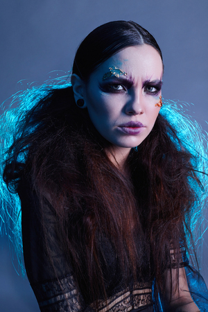 terrible witch woman with halloween make-up. halloween concept. angry mystic girl Stock Photo