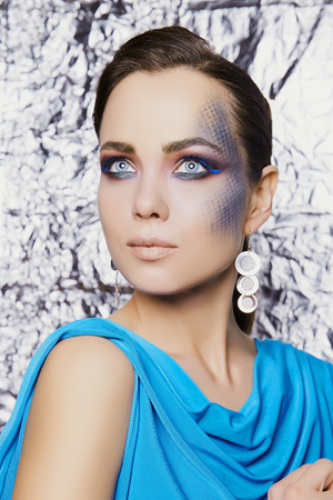 young woman with colorful make-up, over shining foil background. beautiful girl with pattern on her face Reklamní fotografie