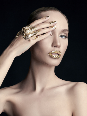 sexy Blonde young woman in golden foil. Beautiful model girl. Reklamní fotografie