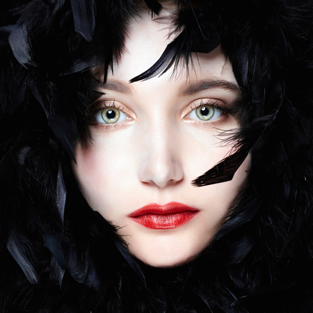 face of beautiful young woman in feathers. Feathers hat girl with make-up