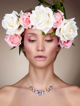 Young woman with flowers in Hair. Beautiful Girl with Rose flowers on her head. Professional make-up Banco de Imagens