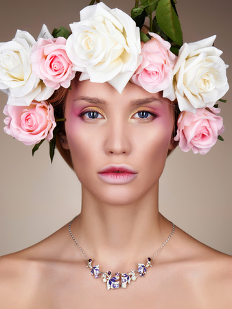 Young woman with flowers in Hair. Beautiful Girl with Rose flowers on her head. Professional make-up Stock Photo