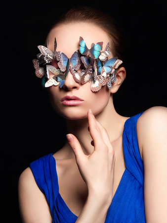 beautiful girl with butterflies on her face. beauty portrait of young woman in unusual mask