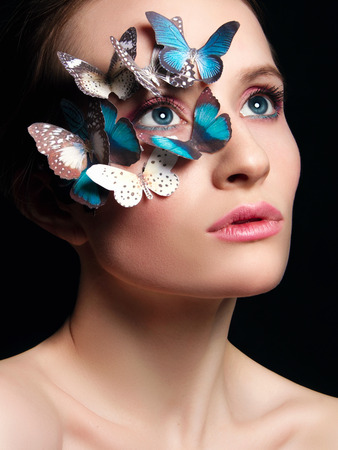 beautiful girl with butterflies on her face. beauty portrait of young woman in unusual mask Stock Photo - 105515661