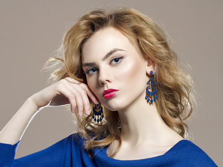 beautiful young woman in jewelry. Blond hair beauty girl with make-up