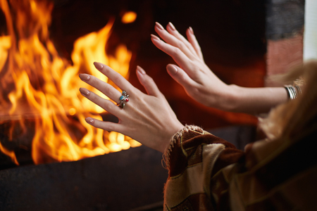 girl is warming her hands by the fire in the fireplace. young woman by the fire Stock Photo - 105515668