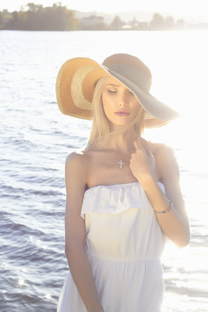 beautiful young blonde woman in hat and white dress. summer sensual beauty girl on the beach, fashion lifestyle outdoors photo