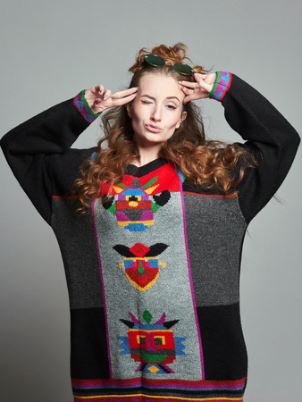 happy hipster girl in sunglasses and colorful sweater. Fashionable lifestyle beautiful young woman Reklamní fotografie