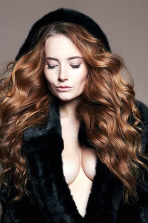 Beautiful young sexy woman in fur hood, healthy hair, curly hairstyle. winter fashion Beauty sexy Model Girl in Luxury Fur coat Stock Photo - 107010072