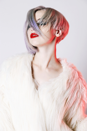 Beautiful young woman with colorful hairstyle, dressed in fur. fashion Beauty sexy Model Girl with trendy color hair and make-up