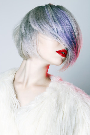 Beautiful Girl with colorful hairstyle, dressed in fur. fashion Beauty Blond Woman with trendy color hair and make-up