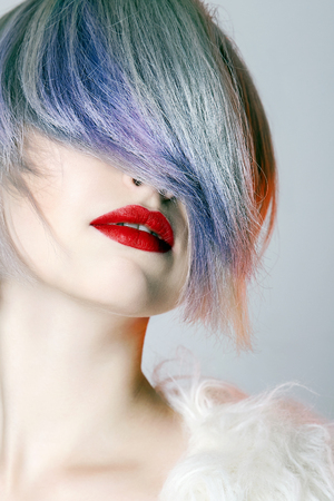 young Woman with colorful Hair, dressed in White Fur. fashion Beauty Model Girl with trendy color hair and red Lips Stockfoto