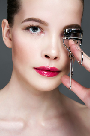 Face of young woman. beautiful girl doing eyelashes. make-up, care concept