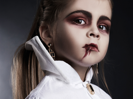 little vimpire child. girl with halloween make-up. dracula kid with blood on her face. halloween holiday children
