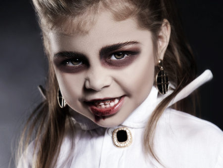 little vimpire child. little angry girl with halloween make-up. dracula kid with blood on her face. halloween holiday children Stockfoto