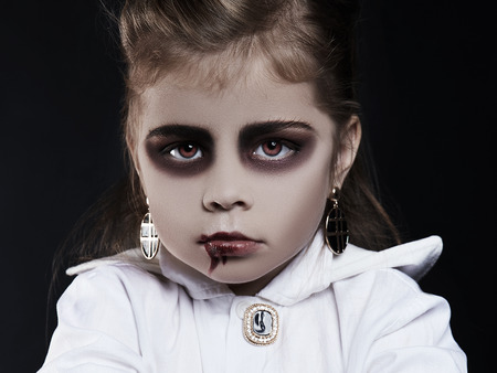 dracula child. little girl with halloween make-up. vimpire kid with blood on her face. halloween holiday children Stock Photo - 107841754