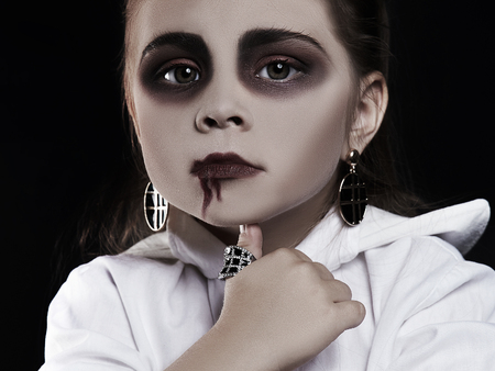 dracula child. little girl with halloween make-up. vimpire kid with blood on her face. halloween holiday children