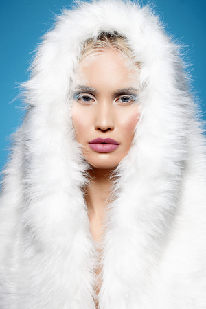 winter girl in fur hood. halloween snow queen make-up. beautiful blond young woman Stock Photo - 109817014