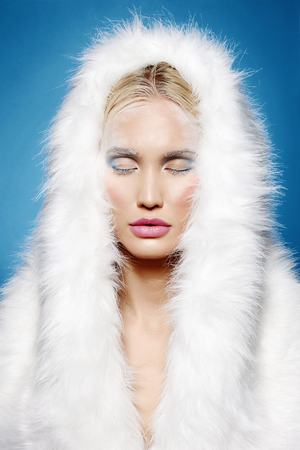 winter girl in fur hood. halloween snow queen make-up. beautiful blond young woman