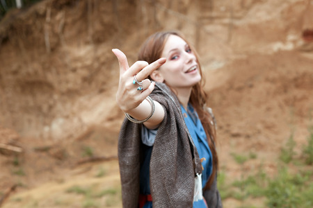 outdoor lifestyle portrait of happy girl. cocky young woman show finger