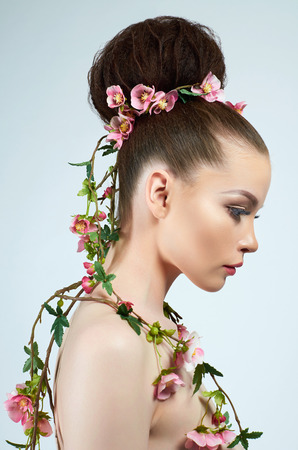 beautiful woman in flowers. model girl with make-up and hairstyle. spring lady plant
