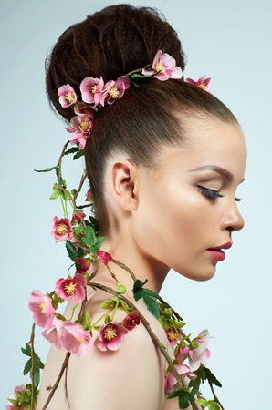 beautiful woman in flowers. model girl with make-up and hairstyle. spring lady plant Reklamní fotografie - 119764840