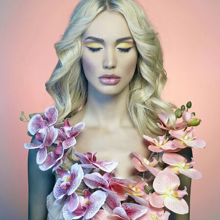 fashion portrait of beautiful blond young woman with orchid flowers.spring colorful beauty girl over pink background