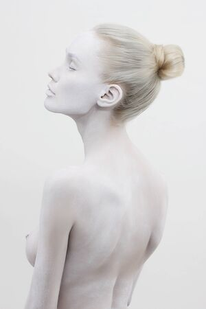 beautiful naked woman in white paint. beautiful nude girl body art