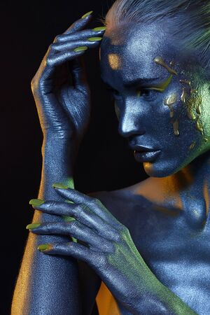 Blue Woman. Beautiful girl in paint. Art portrait in Blue and green Light. make-up. Fairy beauty young woman in color Paint