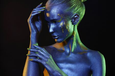 Beautiful girl in paint. Art portrait in Blue and green Light. make-up. Fairy beauty young woman in color Paint Stockfoto - 149142234