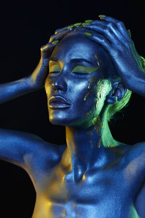 Beautiful girl in paint. Art portrait in Blue and green Light. make-up. Fairy beauty young woman in color Paint Stockfoto - 149142235